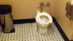 Commode seat, slightly askew. For a fat guy like me, especially one with very short legs, this can be dangerous. I might have been shot clear across the room if that thing had gone out! Luckily, I sat down with great care.